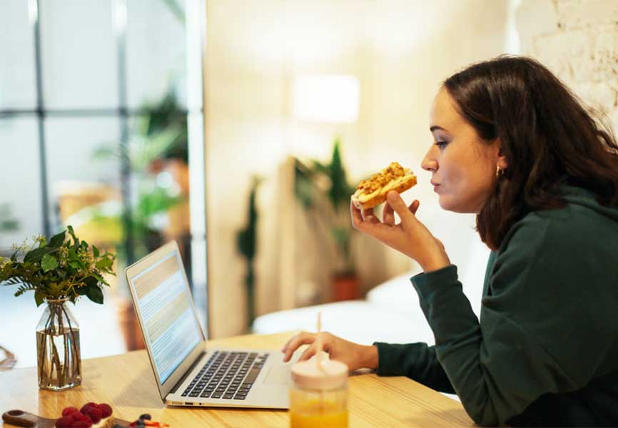 Woman eating at her computer