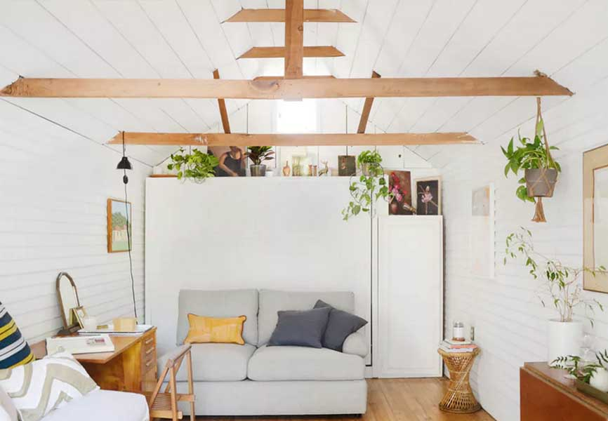 Small white living room with wood rafters