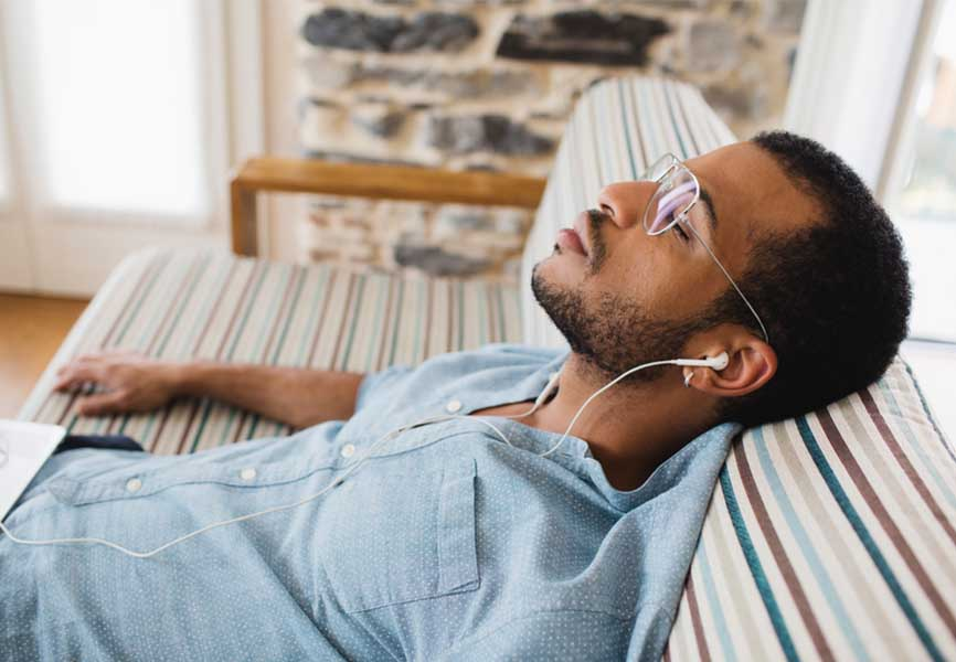 Man sleeping on a couch, with earbuds