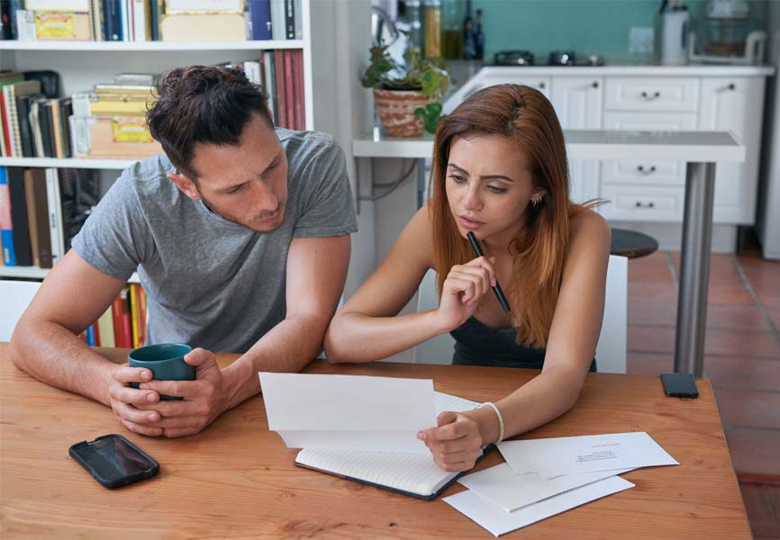 couple sitting at kitchen table looking at papers