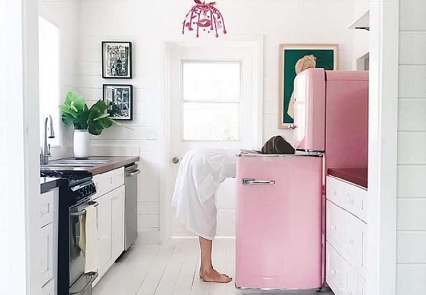 Woman looking in vintage pink fridge