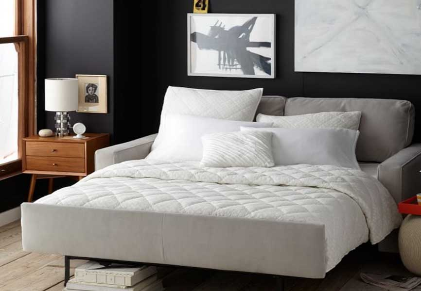 A small white bed in a black room