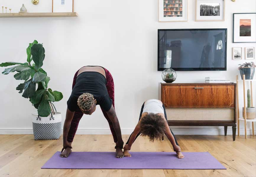 Father and Daughter doing yoga in their living room