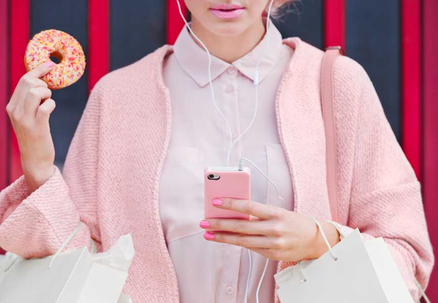 Woman wearing all pink, holding her phone in one hand and a doughnut in the other