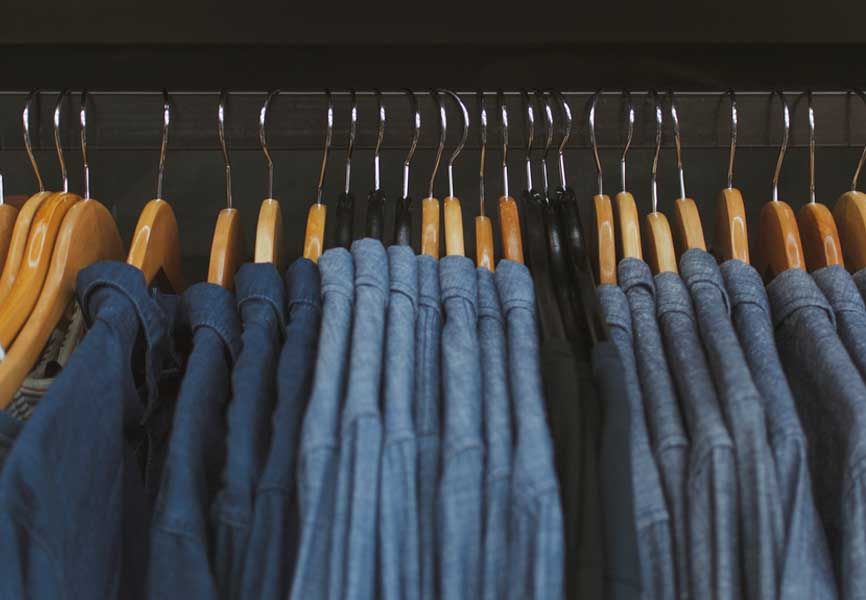 Different shades of blue shirts hanging on a rack