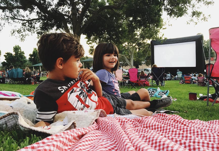 two kids laying on blanket outside with large movie screen behind them