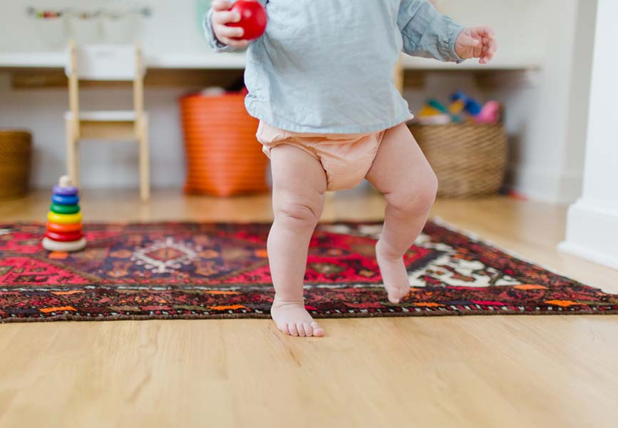 Baby in diaper walking and holding a ball