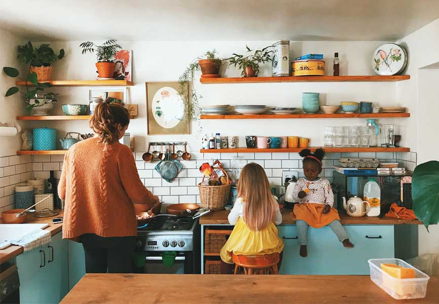 mom and two daughters in open shelving kitchen cooking