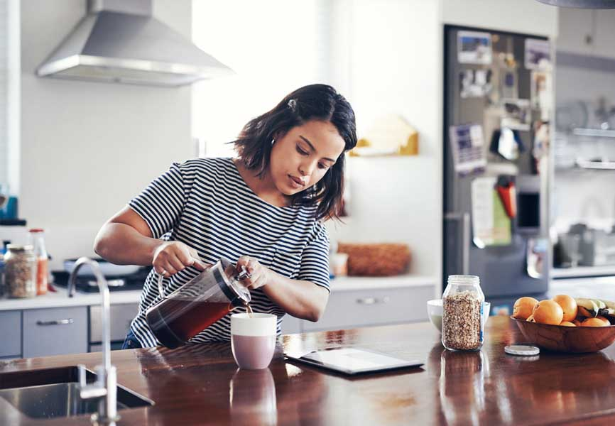 girl in kitchen pouring coffee into a mug