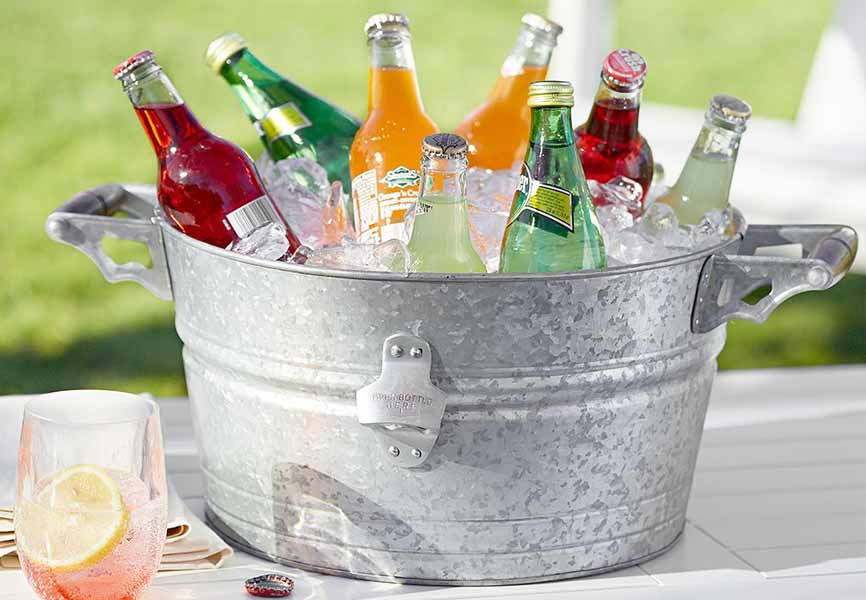 metal bucket with different drinks and ice inside