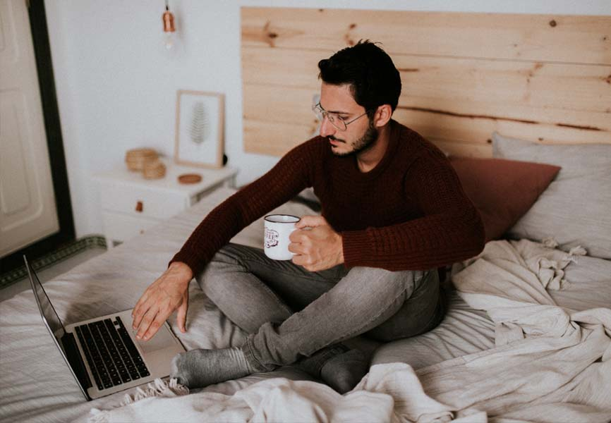 man sitting on bed holding cup of coffee looking at laptop