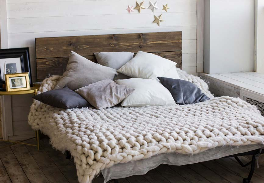 bed with rustic wood headboard and cozy chunky knit blanket and pillows