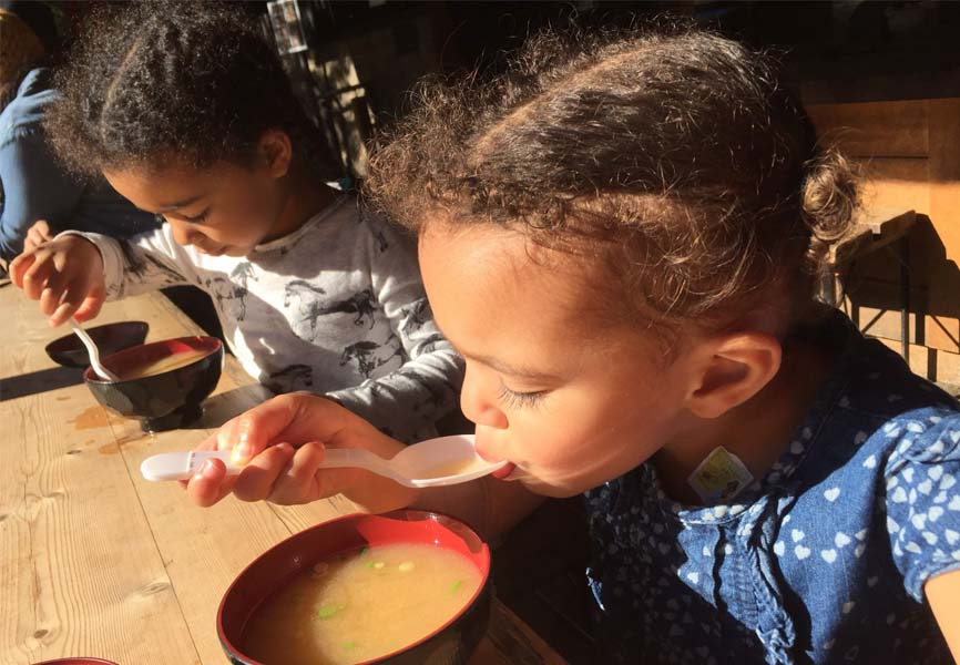 two children eating soup at a wooden table