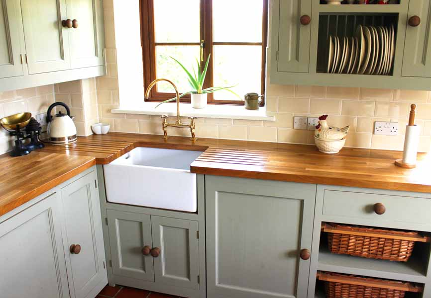 mint coloured kitchen with wood counters and plants