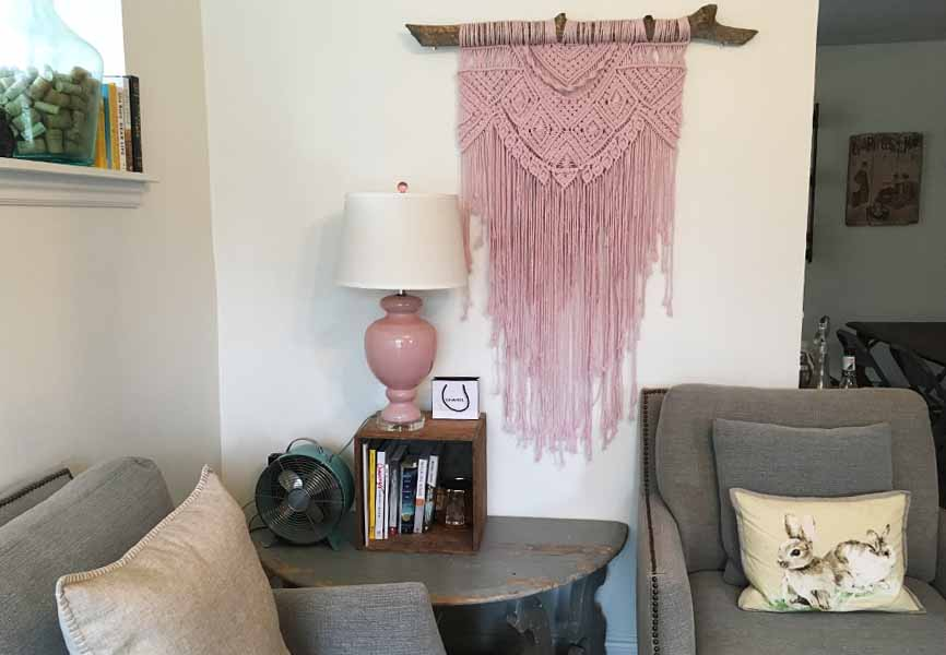 pink macrame on the wall and small vintage fan on a table