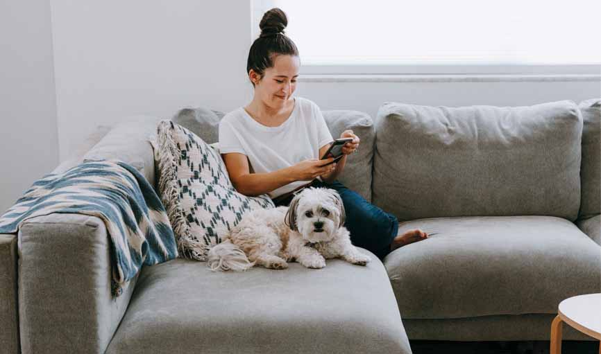 lady on couch with her dog on her phone smiling