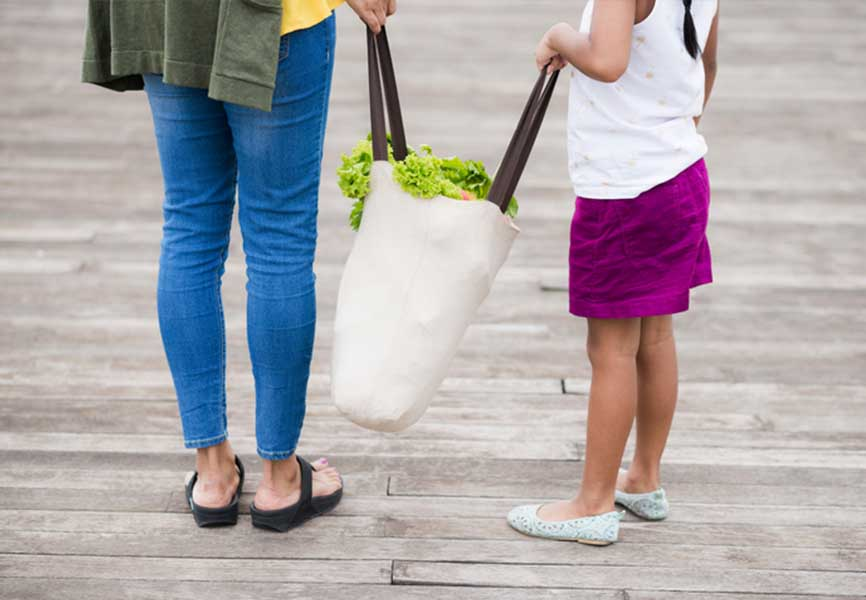 Mother and daughter holding a full reusable grocery bag