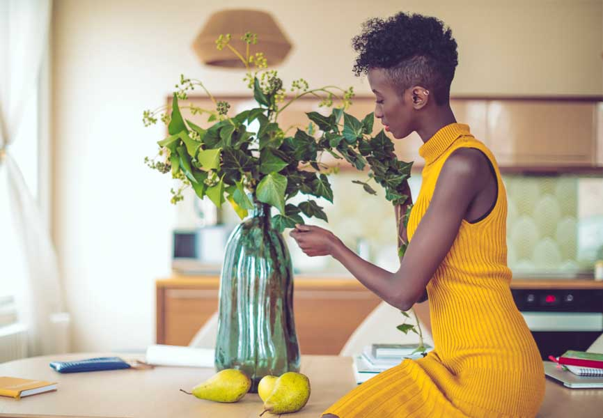 woman wearing yellow organizing plant arrangement