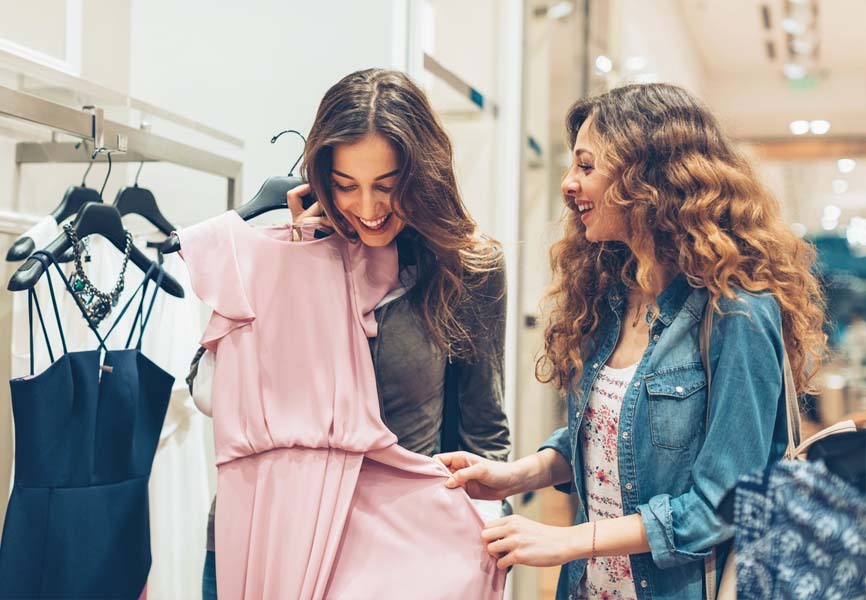 two girls holding up pink dress while shopping
