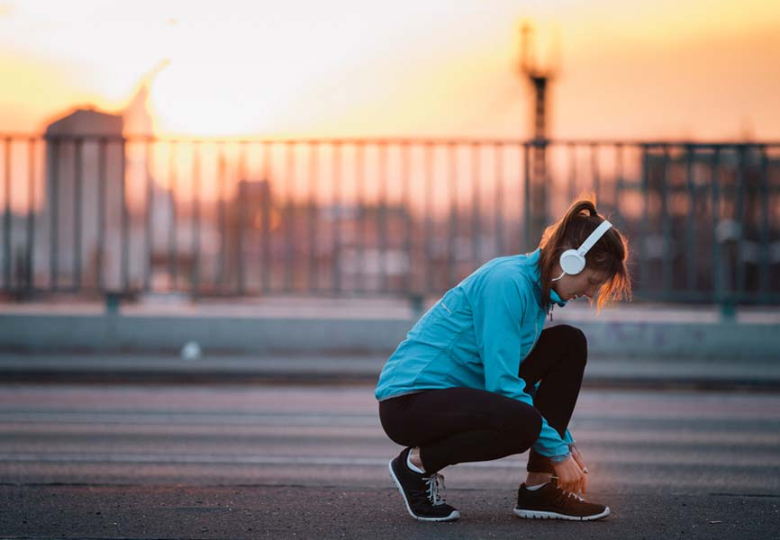 girl on jog stopped to tie laces wearing headphones with sunset background