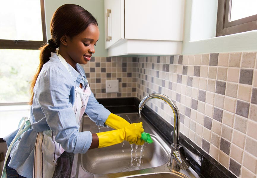 girl standing at sink with yellow rubber gloves rinsing a cleaning sponge