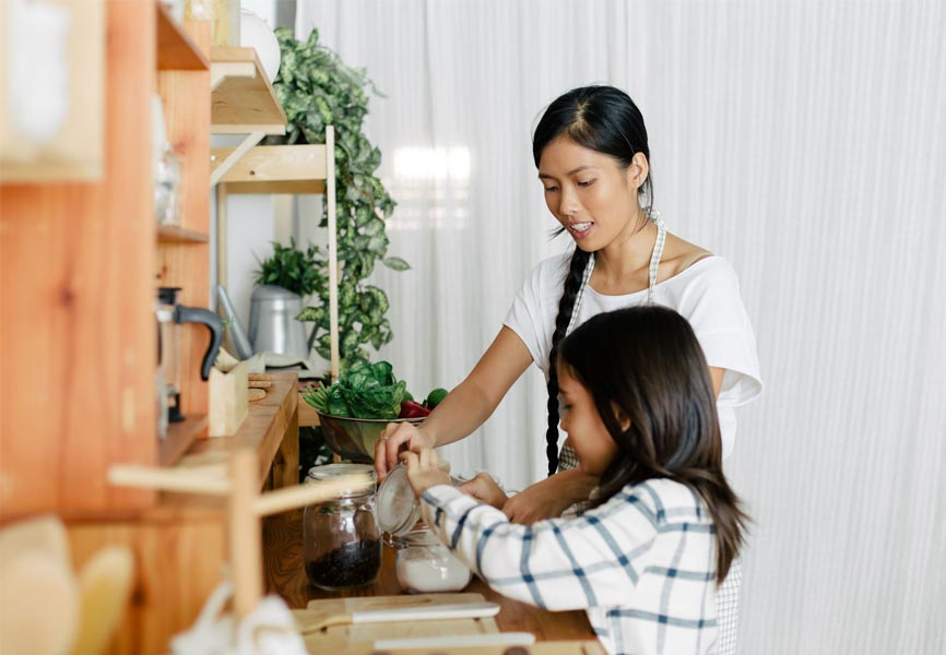 mother and daughter putting sugar in a jar on the counter