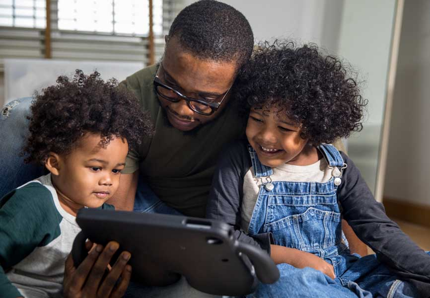 dad with two young kids looking at an iPad and smiling
