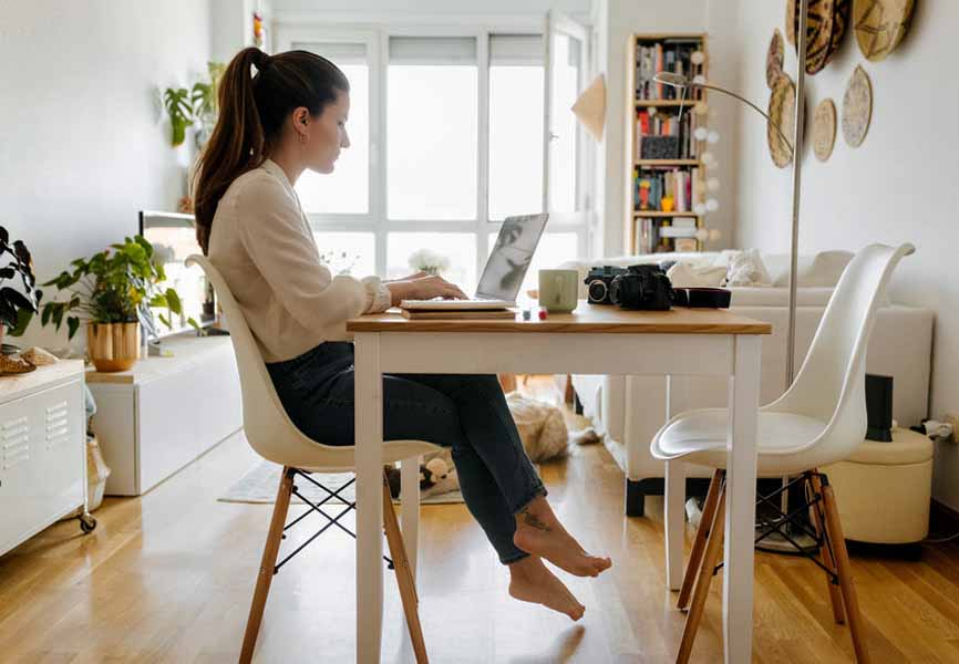 girl sitting at desk in small, bright apartment