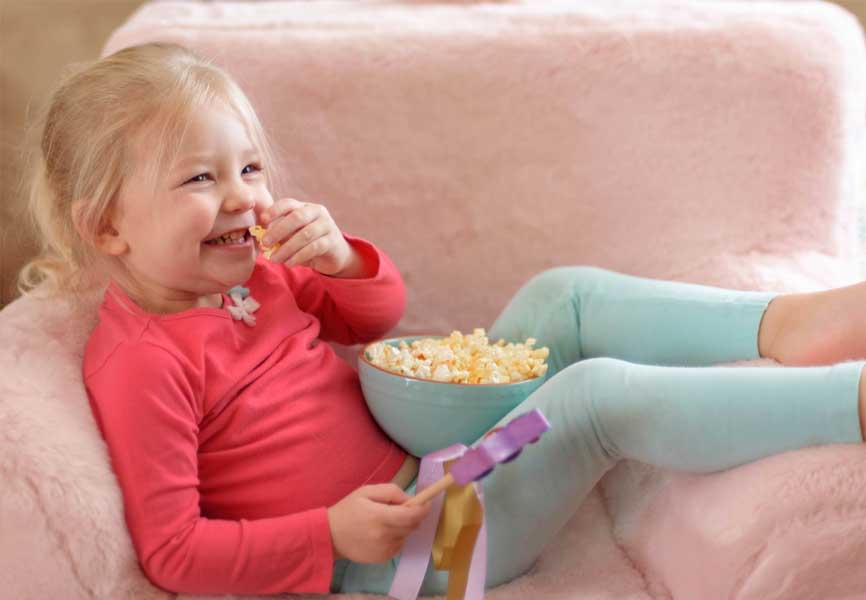 little blonde girl in pink top sitting on couch eating popcorn