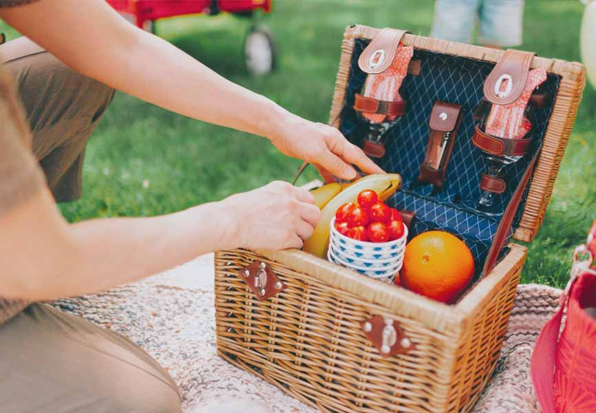 picnic basket with cherry tomatoes and bananas in it