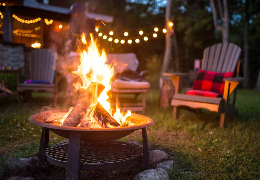 fireplace at cottage with muskoka chairs around it