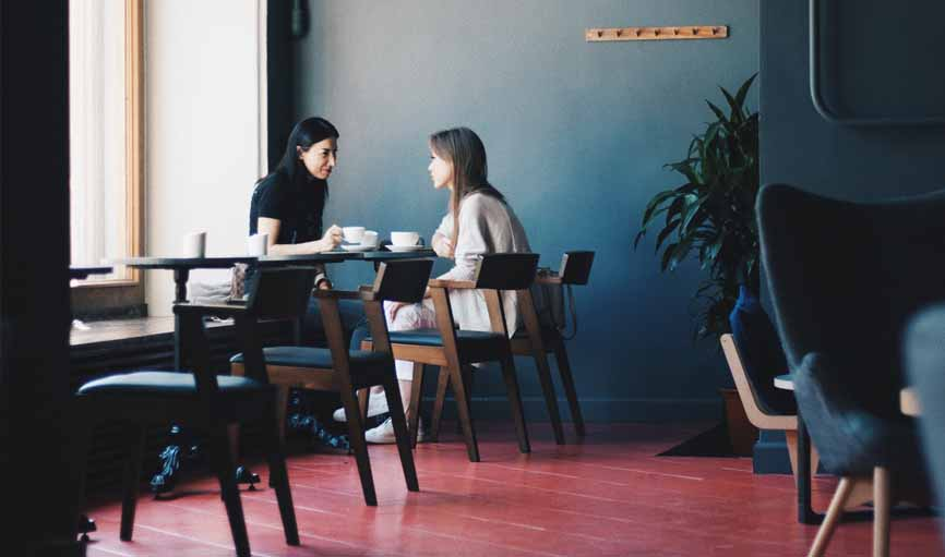 two ladies chatting at a coffee shop