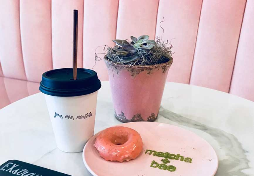 pink donut on plate with drink with reusable straw in it