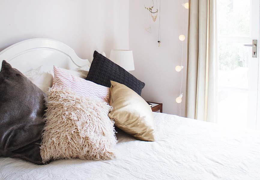 cozy white bed with fluffy white and grey pillows and string lights