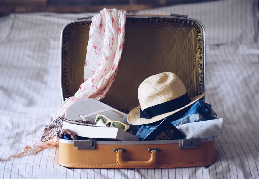suitcase open on bed with scarf, hat, book and passport inside