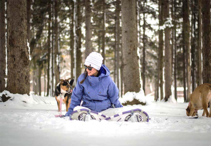 girl sitting in snow in forest with two dogs