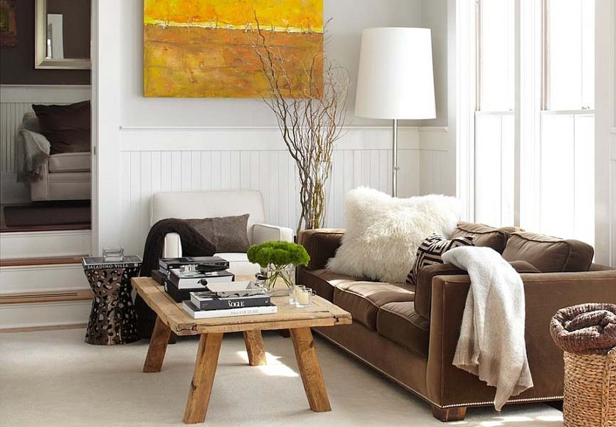 living room with bright yellow painting, cozy couch blankets and a wooden coffee table