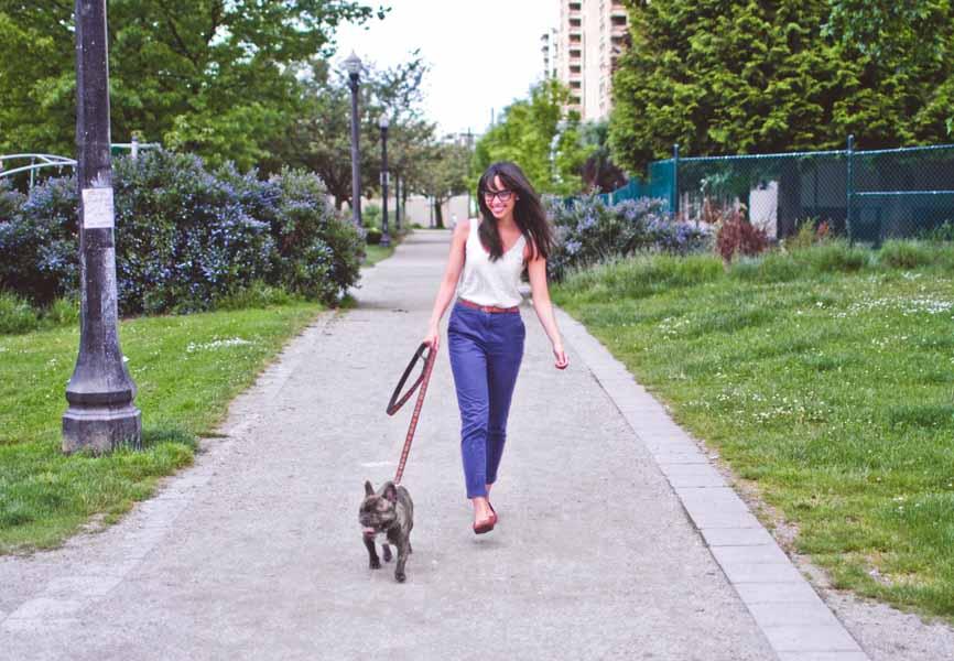 girl walking french bulldog along path in park