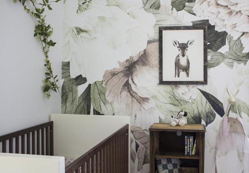 baby's room with blush floral wallpaper mural on wall in background