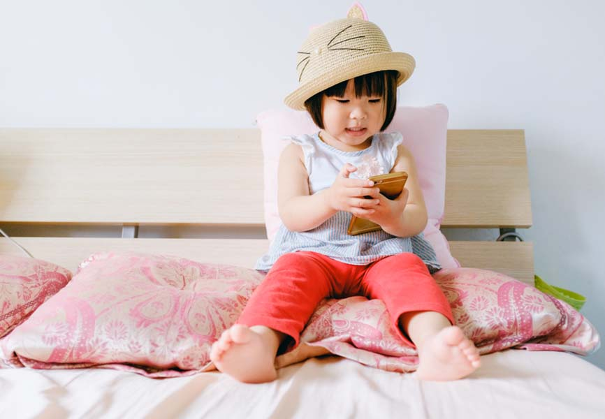 Little girl using a smartphone on a bed
