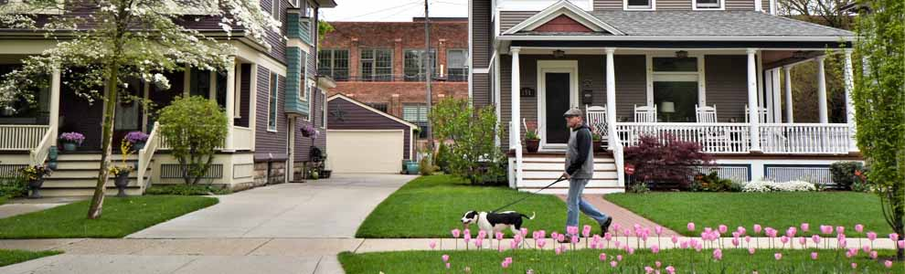 man walking dog on street in front of nice porch on home