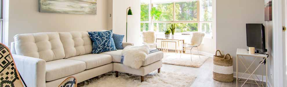 small apartment with white fluffy carpet and beige sofa