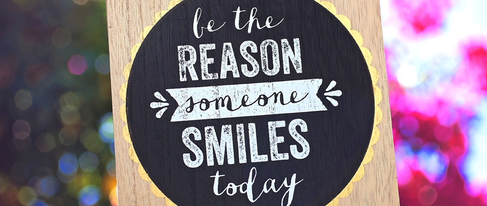 sign that says be the reason someone smiles today