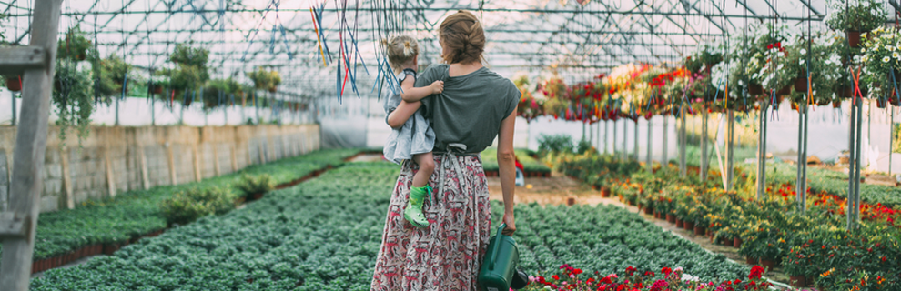 woman in skirt holding child on her left hip, standing in large community garden holding a watering can