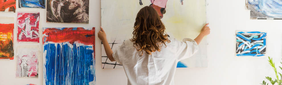 A woman hanging up paintings