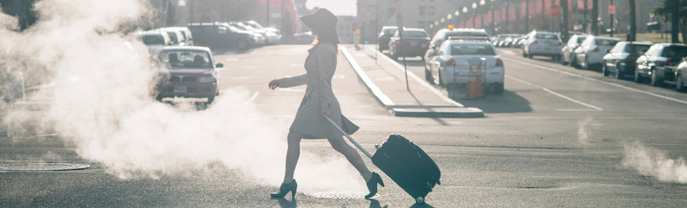 girl in heels, dress and hat crossing street pulling suitcase