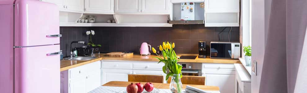 kitchen with pink fridge and yellow tulips on table