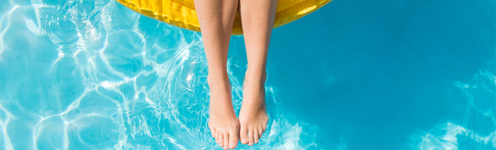 woman's legs only, floating in pool on yellow inflatable pool toy