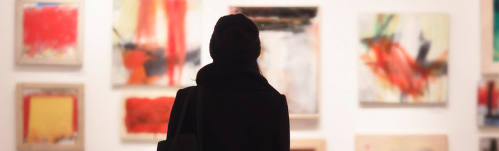 shadow of a woman looking at a wall of art in a gallery