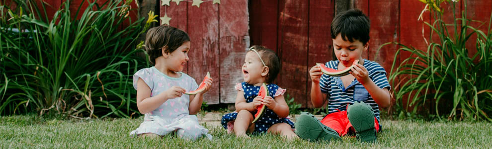three toddlers sitting outside in the grass eating watermelon